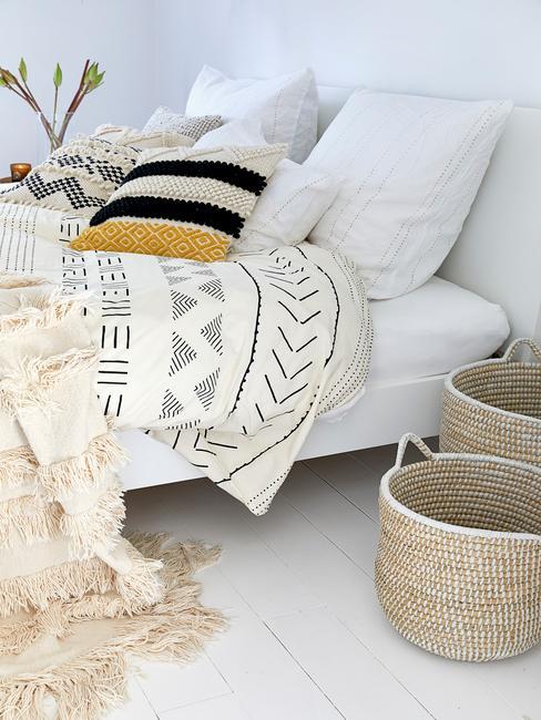 Zbliżenie na łóżko w sypialni, z białym kocem we wzory i rattanowe kosze