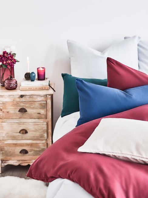 Łożko z różnokolorowymi poduszkami, bordową kołdrą oraz rustykalną szafką nocną