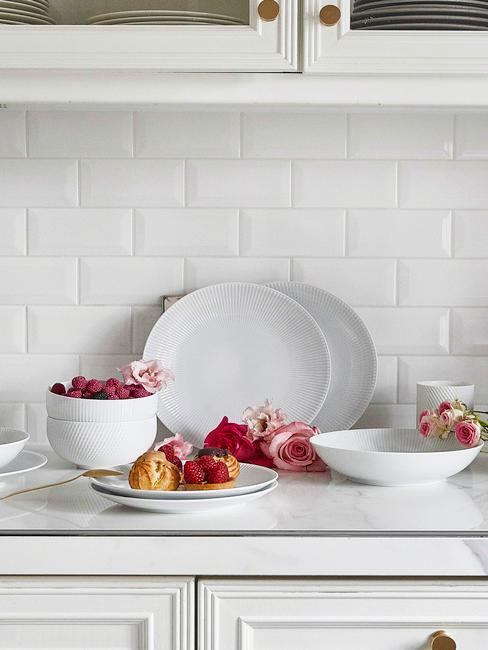 Biała kuchnia z białym blatem i płytkami oraz białą zastawą obiadową