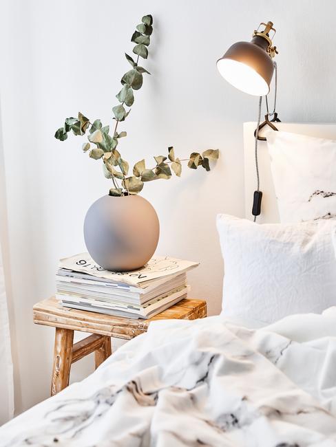 Stolik na łożko w postaci taboretu z gazetami, okrągłą doniczką oraz eukaliptusem