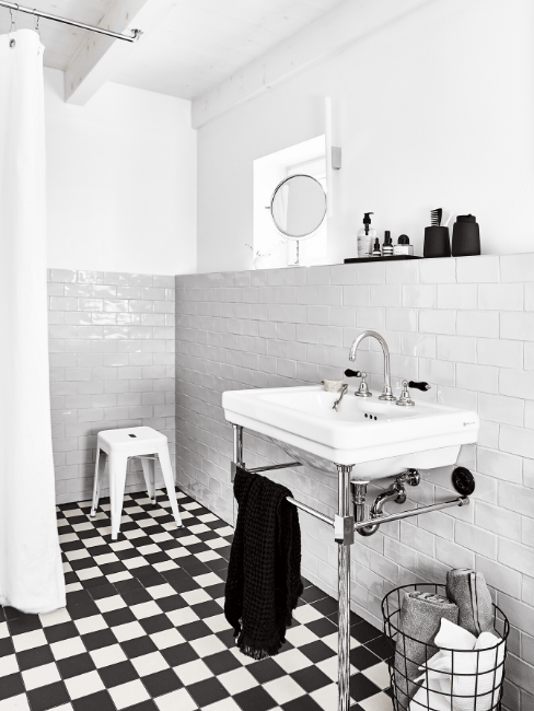Czarno-biała łazienka z płytkami, prysznicem oraz zlewem