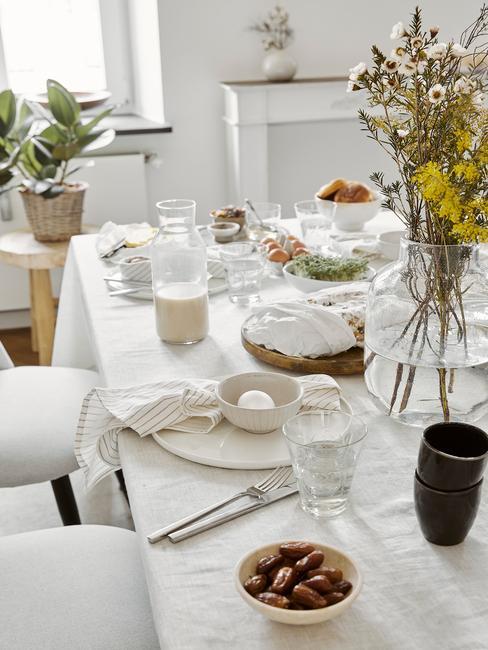 Zbliżenie na stół udekorowany na biało, z białą zastawą, roślinami w wazonach oraz dekoracjami