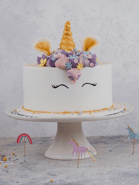 Biały tort z motywem jednorożca stojący na paterze