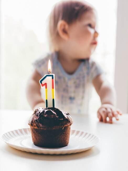 Zbliżenie na chłopca przed babeczką ze świeczką urodzinową na pierwsze urodziny