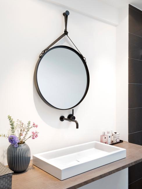 Biały zlew, czarne wiszące lustor oraz wazon z kwiatami w łazience