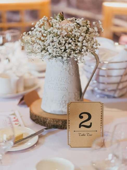 Aranżacja stołu weselnego w stylu vingate z konwaliami w białym dzbanku