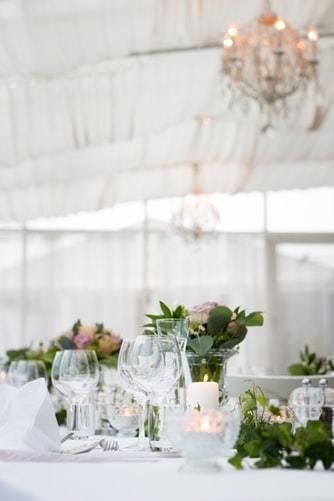 Zastawiony stół weselny z niską aranżacją kwiatową