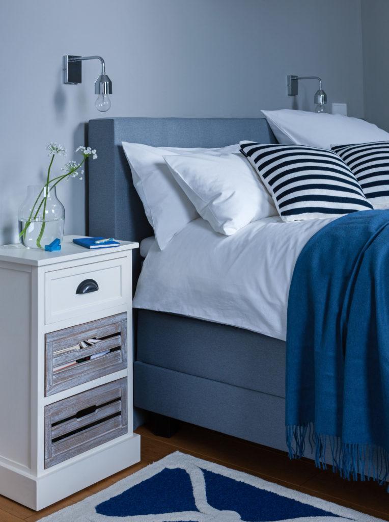 Granatowa sypialnia z podwójnym łożkie, białą szafką nocną oraz poduszkami dekoracyjnymi