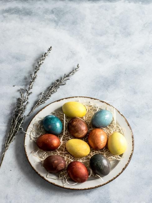 Pomalowane jajka ułożone na białym talerzy obok gałązek suszonej lawendy