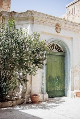 Zielone drzwi wejściowe w białym budynku oraz drzewo