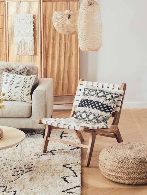 Rattanowe krzesło z poduszką, beżowa sofa, beżowy dywan oraz lampy w salonie