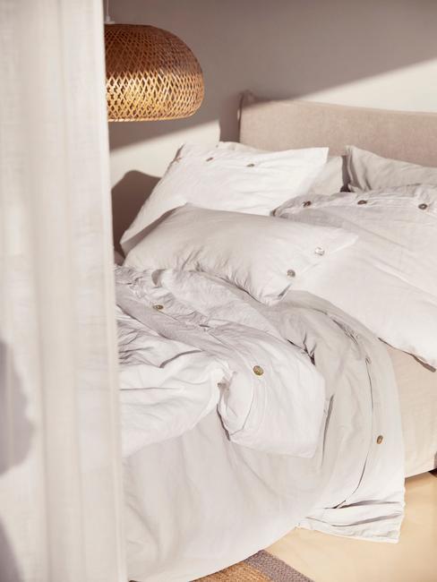 Łóżko z lnianą pościelą, nad nim pleciona lampa