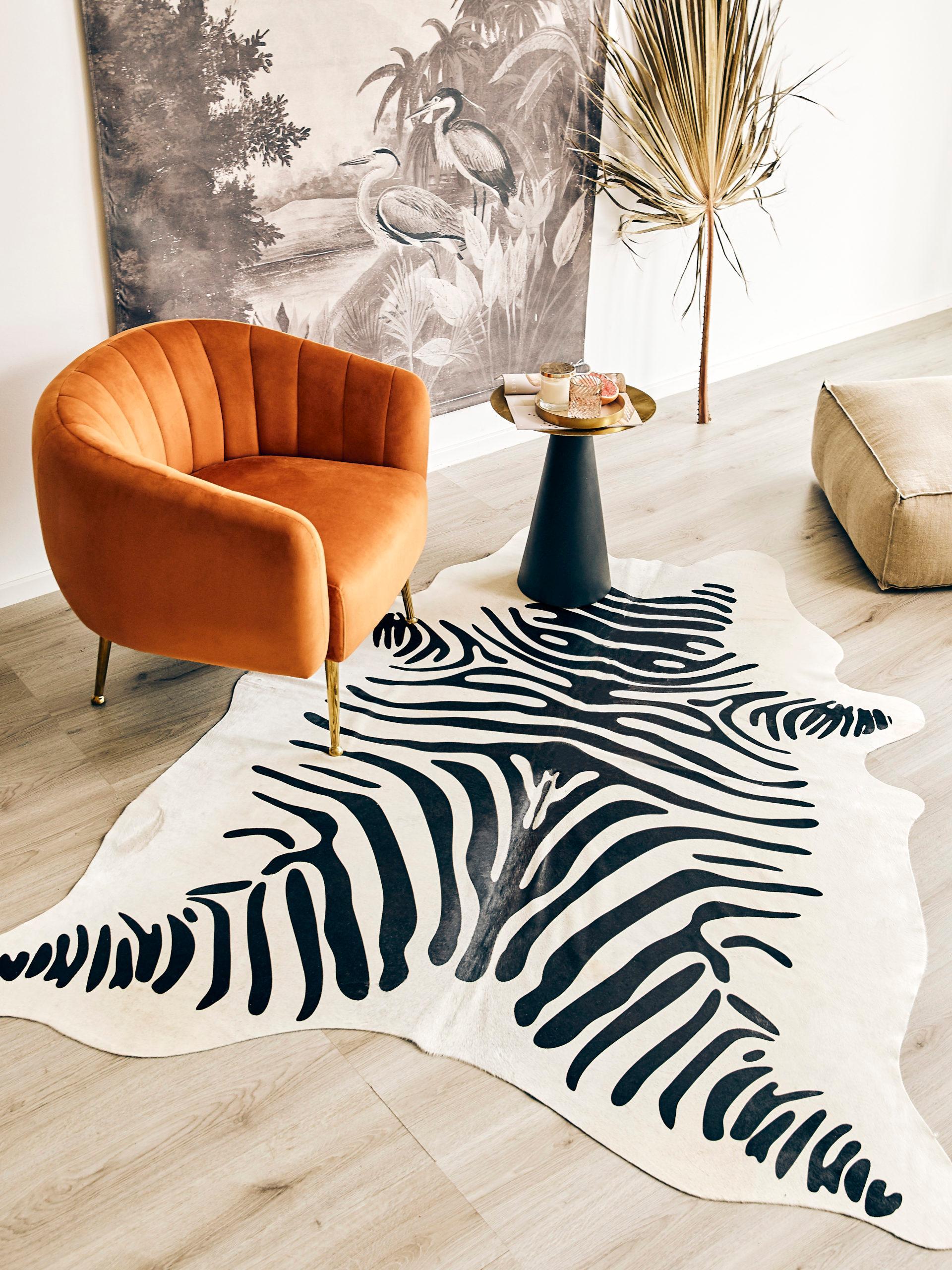 Dywan w zebrę, pomarańczowy fotel oraz fototapeta