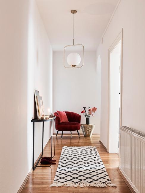 Przedpokój z dywanem oraz burgundowym krzesłem i wazonem