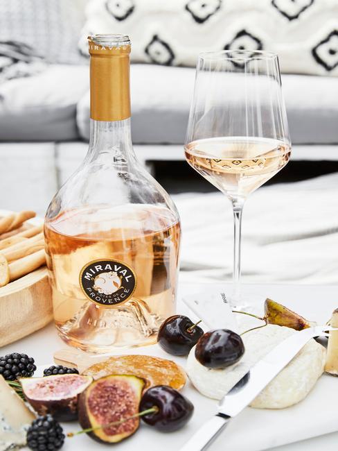 Butelka szampana i ieliszek z owocami stojące na stole