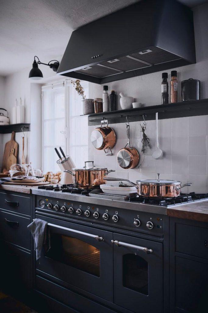 Czarna kuchnia z półkami oraz akcesoriami kuchennymi