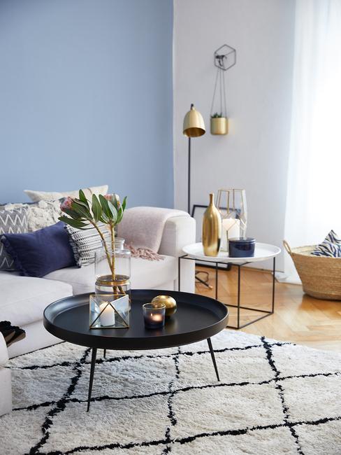 Fragment biało-niebieskiego salonu z białą kanapą, czarnym stolikiem oraz złotą lampą