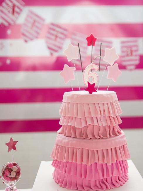 Różowy tort urodzinowy z różowymi dekoracjami pomieszczenia