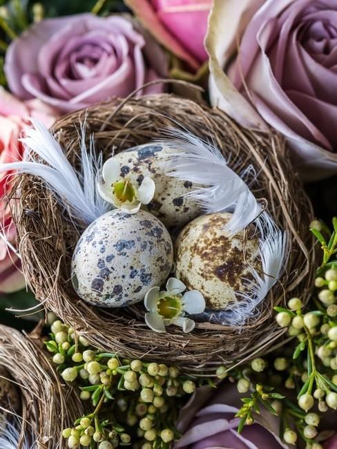 Koszyczek wielkanocny z jajkami udekorowany piórkami oraz kwiatami