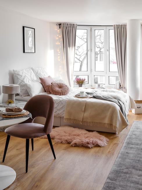 Sypialnia z łóżkiem, krzesłem, stolikiem oraz załonami w oknach