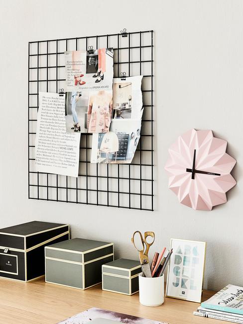 Drewniane biurko w pudełkami na organizację rzeczy oraz wisząca nad nim tablica moodboard