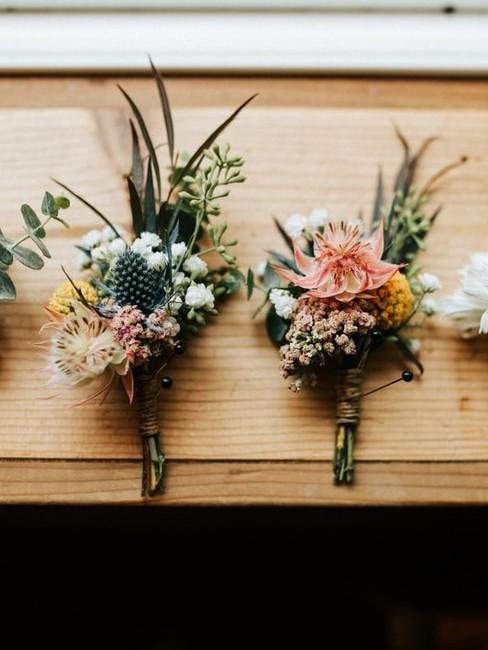 Dwa małe bukieciki ślubne leżąca na drewnianym stole
