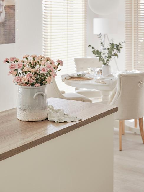 Jadalnia ze stołem i czterema krzesłami oraz wyspą kuchenną, na której znajduje się wazon z kwiatami
