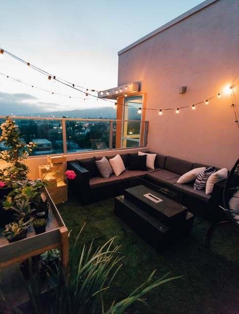 Duży balkon z narożna kanapą ogrodową oraz girlandą świetlną