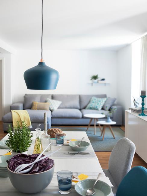 Salon połączony z jadalnia, z szarą sofą, białym stołkiem i dodatkami w różnych odcieniach niebieskiego