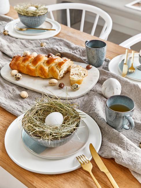Zbliżenie na drewniany stół z białymi i niebieskimi talerzami oraz złotymi sztućcami