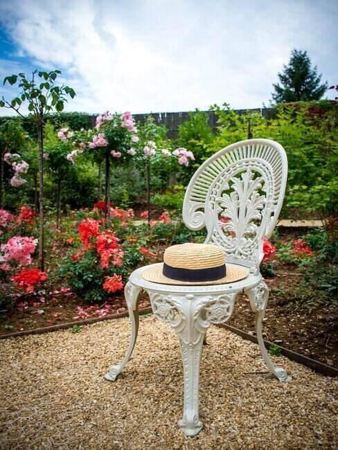 Krzesło stojące w ogrodzie z położonym kapeluszem