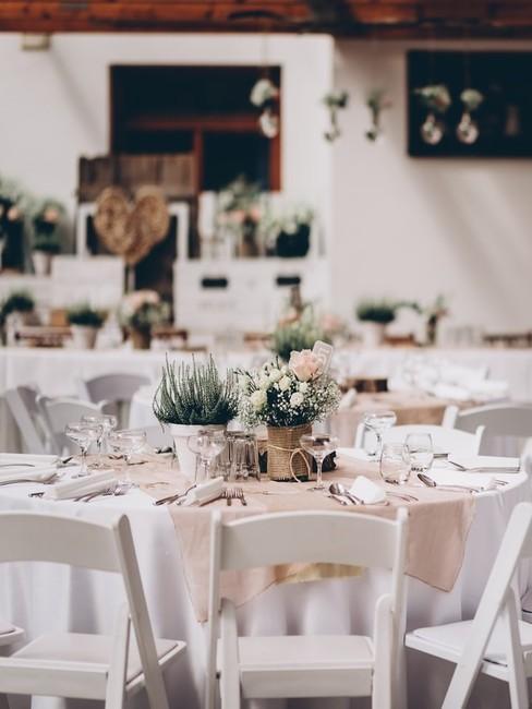Fragment sali weselnej z okrągłymi stołami, na których znajduje się zastawa oraz dekoracje