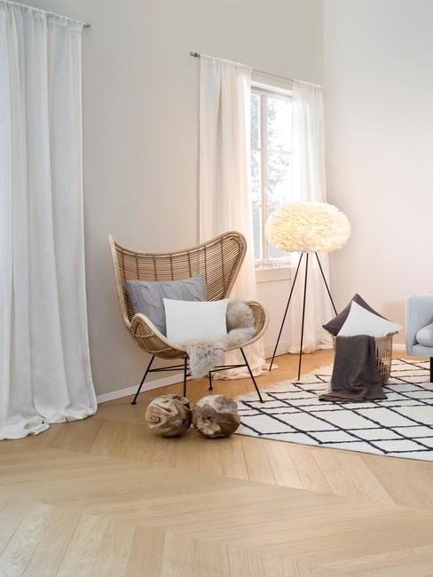 Fragment salonu w stylu rustykalnym z ażurowym fotelem i lampą