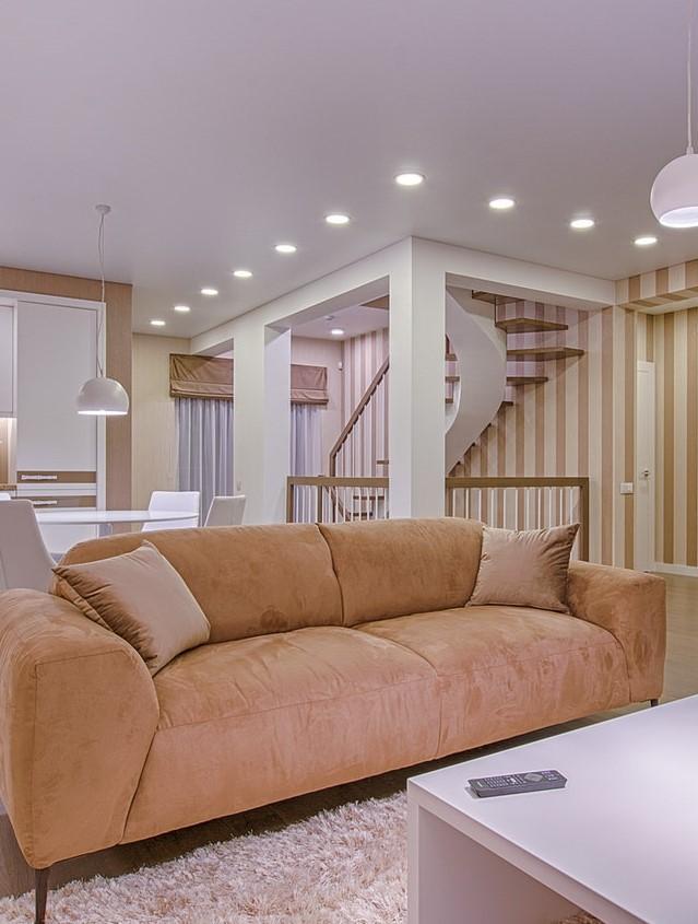 Salon z beżową kanapą, stolikiem kawowym oraz oświetlonymi schodami