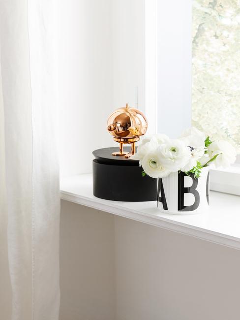 Parapet w sypialni z czarnym pudełkiem, mosiężnym elementem oraz wazonem z kwiatami