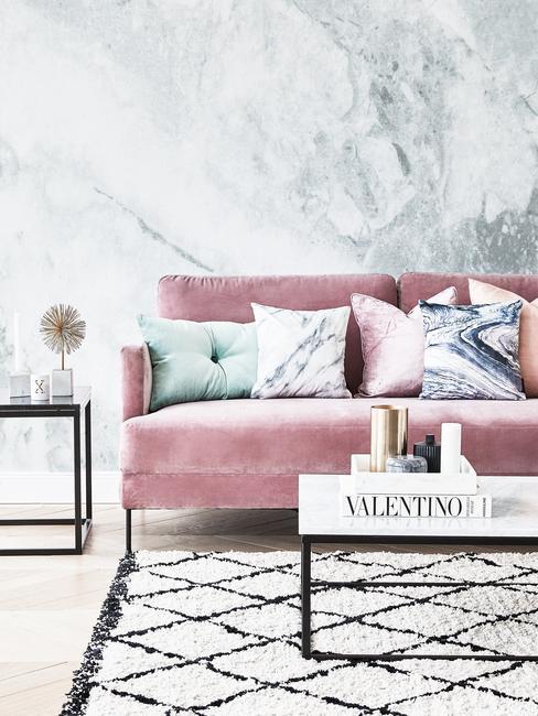 Salon z różową kanapą, czarno-białym dywanem oraz stolikiem kawowym