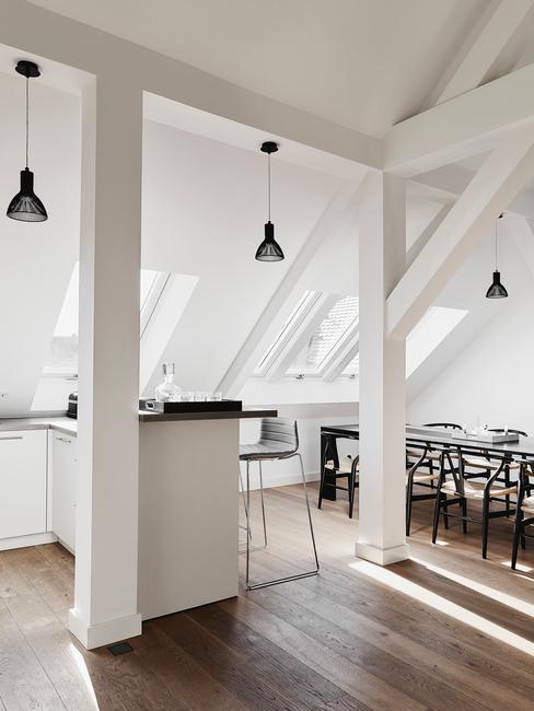 Kuchnia na poddaszu z białymi belkami i czarnymi lampami