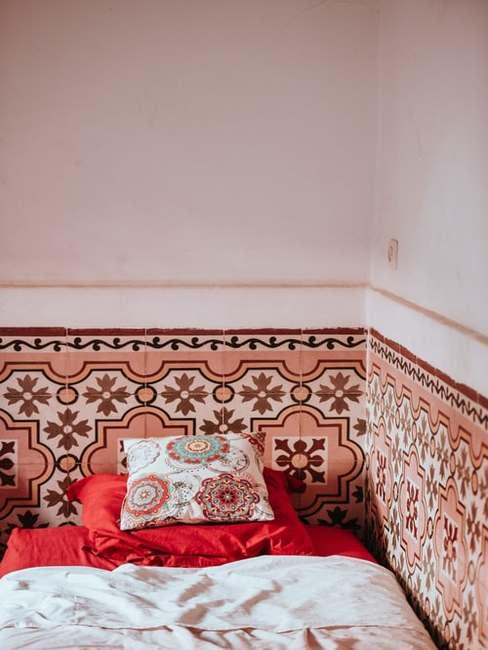 Sypialnia wyłożona w kolorowe płytki z łożkiem