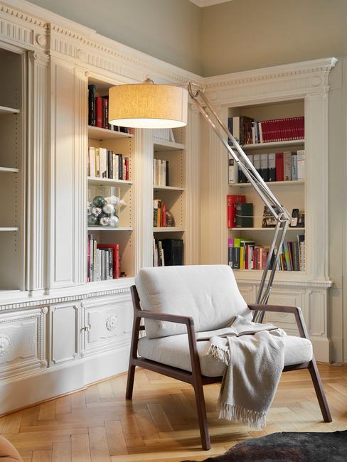 Biały fotel stojący na tle biblioteczkiw salonie