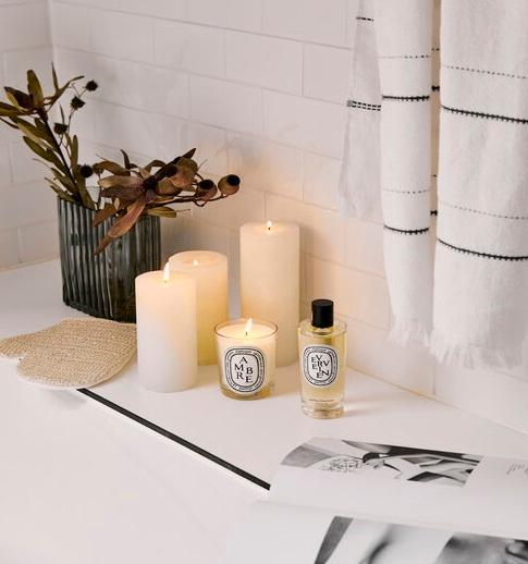 Świeczki ustawione na półce w białej łazience