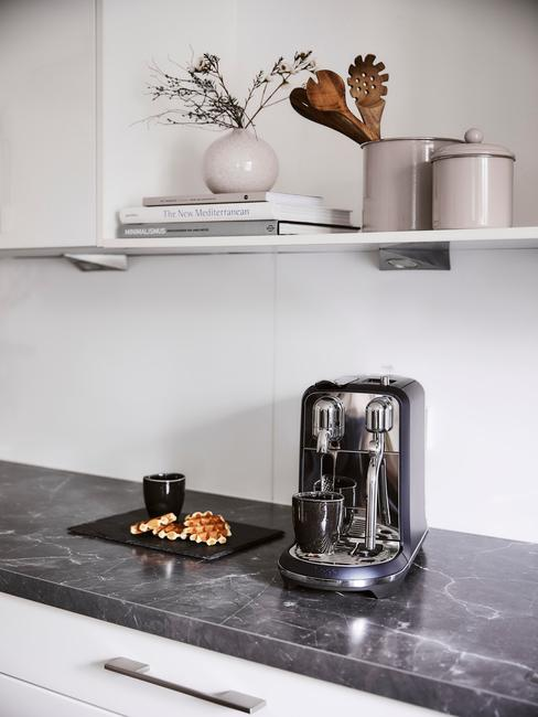 Kuchnia industrialna z czarnym, marmurowym blatem oraz srebrnym ekspresem do kawy