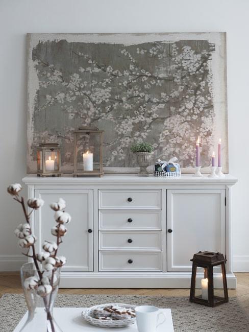 Komoda w salonie w stylu rustykalnym, na której stoją zapalone świece