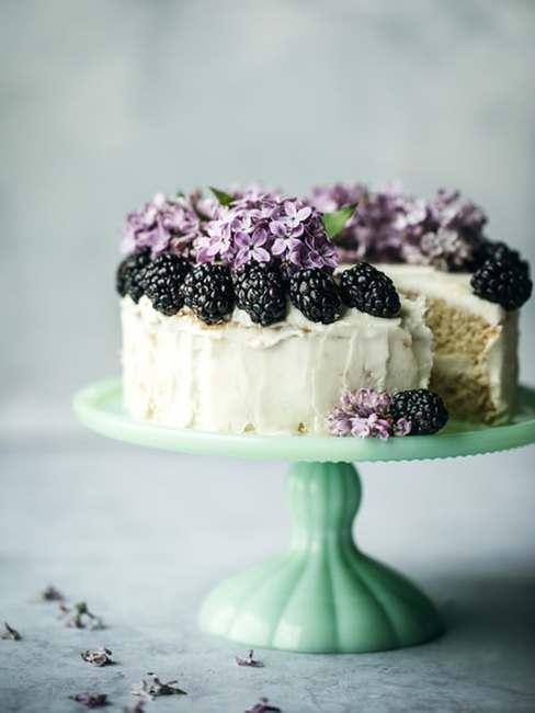 Tort udekorowanay jeżynami oraz kwiatami bzu ułożony na białej paterze