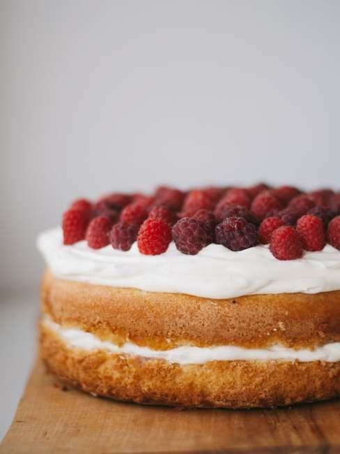 Dwuwarstwowy tort z białym kremem udekorowany za pomocą owoców