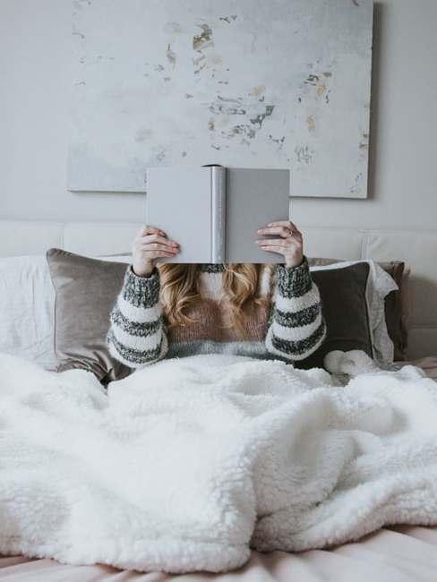 Dziewczyna czytające książkę pod białym kocem w salonie o białych ścianach