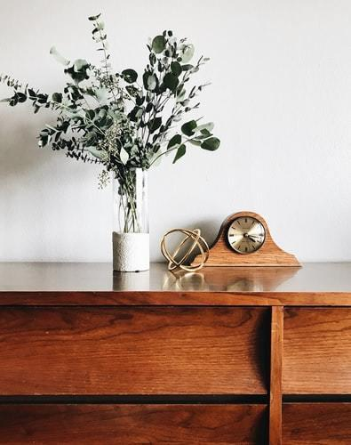 Drewniana komoda, na której stoi wazon z kwiatami oraz zegar