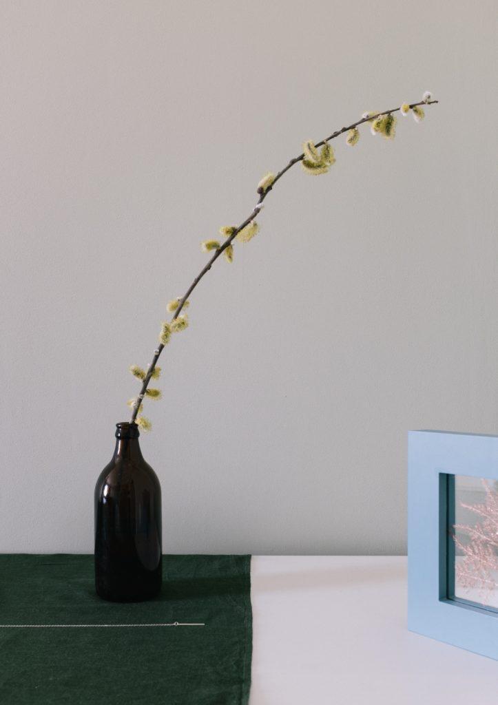 Gałązka rośliny w czarnym waznie w kształcie butelki na czarnym stole