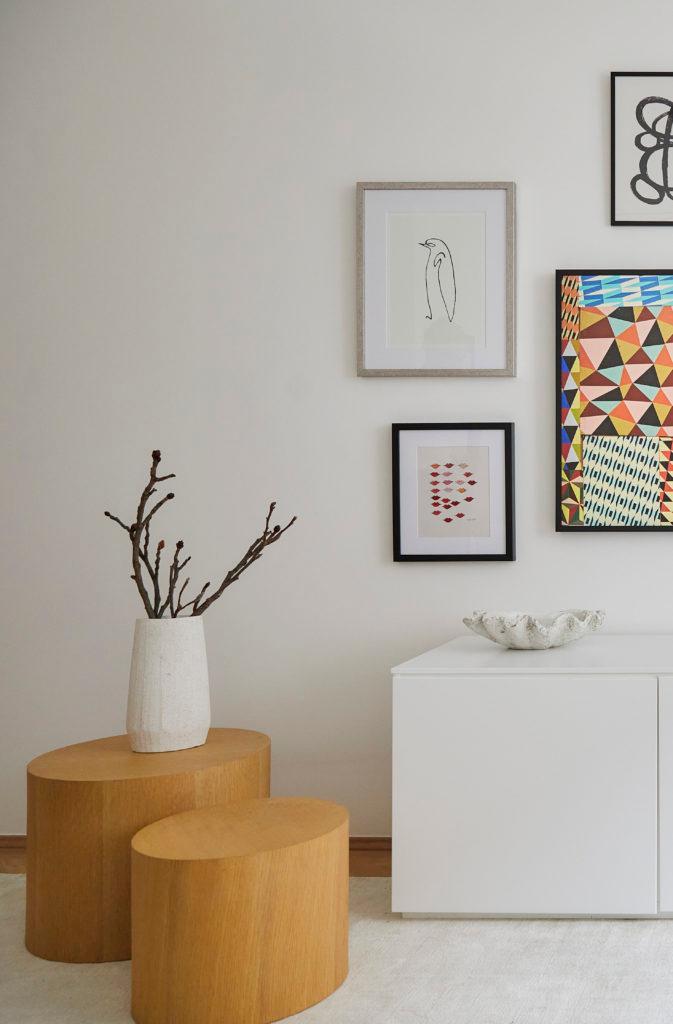 Jasny salon z galerią ścienną, dwa drewniane stoliczki pomocnicze, na którym jest biały wazon z gałązkami