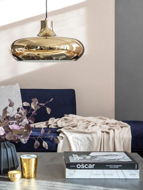 Sofa w kolorze kobaltu a nad nią lampa ze złotym żyrandolem