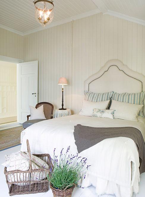 Sypialnia w stylu prowansalskim w bieli z koszami lawendy przed łóżkiem